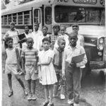 African-American children in front of school bus, 1965